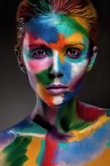 Fashion model girl portrait with colorful paint make up. Sexy woman bright color makeup. Art design. Grey background