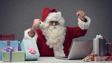 Cheerful Santa connecting with his laptop