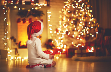 child girl  sitting  back in front of  Christmas tree on Christmas Eve Wall mural