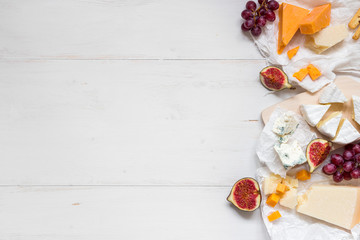 Various types of cheese with fruits on the wooden white table with copy space. Top view
