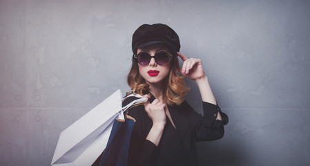 Style redhead girl in hat with shopping bags and sunglasses