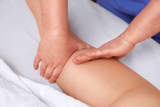 The masseur makes Anti-cellulite massage on the buttock and thighs of the patient. Treatment of excess weight.