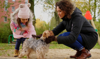 Mother and daughter playing with dog on playground