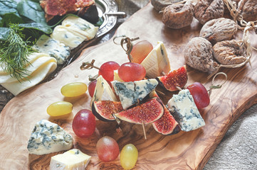 Italian Focaccia bread with cheese and a cheese plate with figs and Gorgonzola, brie, DorBlu and grapes.