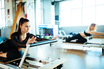 Two young females doing reformer exercises on pilates machines