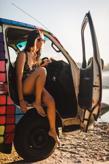 Woman sitting inside a Van, looking sunset