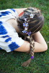 Girl laying in the grass with a french braid and flowers in her hair
