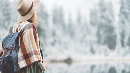 Young traveling woman enjoying wilderness in front of incredible mountain lake. Wearing hat, poncho and backpack. Winter is coming, first snowfall. Wanderlust and boho style
