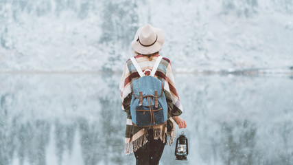 Young woman standing in the wild in front of amazing natural lake view with kerosene lamp. Wearing hat, poncho and backpack. Winter is coming, first snowfall. Wanderlust and boho style