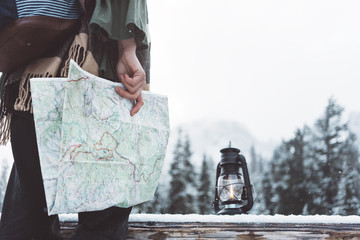 Woman standing in the wild with map and oil lamp. Close-up. Winter is coming, first snowfall. Wanderlust and boho style