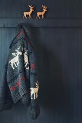 Vintage wool knit Cowichan sweater hanging on coak hook