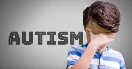 Boy against grey background with autism text