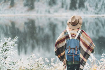 Young traveling girl standing in front of beautiful mountain lake. Winter is coming, first snowfall. Wanderlust and boho style