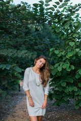 Beautiful woman in a sweater dress standing outside by a tree