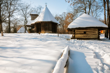 A small wooden church and cottage covered in snow at the Village Museum, an open-air ethnographic museum located in Bucharest, Romania.