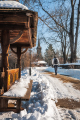 Winter walk in a snow-covered street with a traditional wooden Church at the Village Museum in Bucharest, Romania