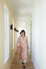 Stylish woman walking down hallway of modern design home