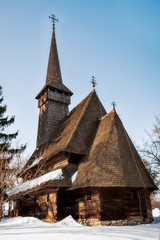 Traditional wooden Church with a bell tower surrounded by snow at the open-air ethnographic Village Museum in Bucharest, Romania