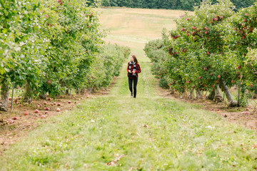 Young Woman Walking in Apple Orchard