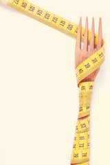 Wooden fork wrapped in centimeter, concept of lose weight and healthy lifestyle
