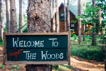 A Welcome Sign By A Log Cabin in the Woods