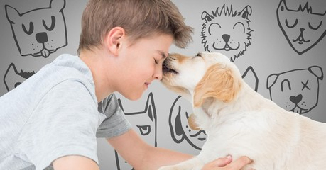 Boy against grey background with friendly dog licking his face