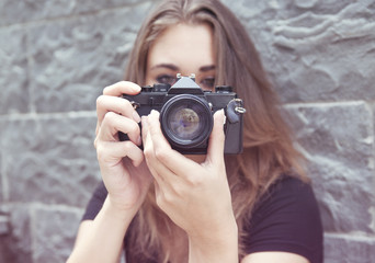 Young woman taking a picture with a vintage camera