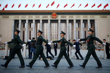 Paramilitary police march past the Great Hall of the People before the start of the closing session of the 19th National Congress of the Communist Party of China