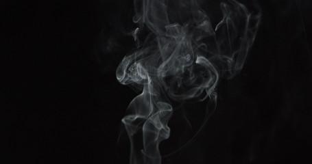 Wispy clouds of smoke over center of dark background