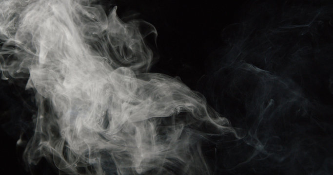 Wispy tower of smoke on left side of dark background