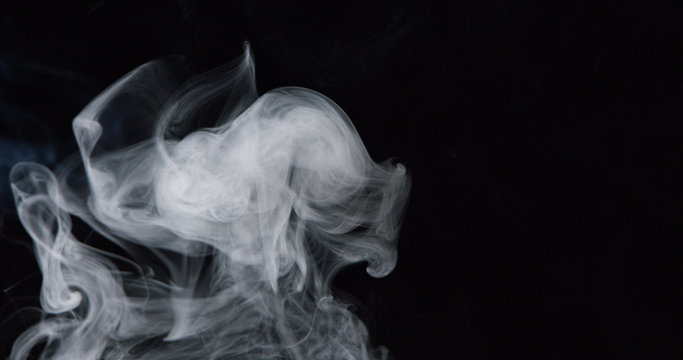 Billowing cloud of white smoke against dark background 2