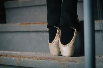 detail of ballet dancer's feet in an urban warehouse setting.
