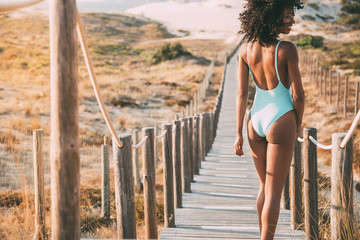 Young woman with a swimming suit walking in a wooden foot bridge at the beach