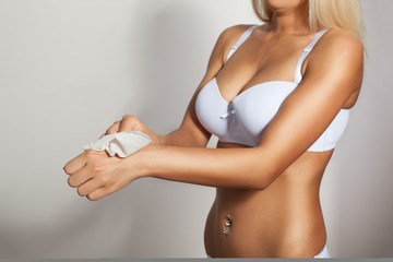 Young woman in white lingerie cleaning hands with wet wipes