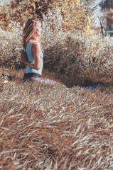 Pretty blond girl stretching and practicing yoga exercises outside in nature