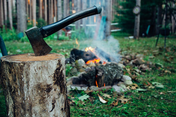 Hatchet in a Wood Stump By A Camping Fire