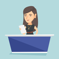 Young caucasian television anchorwoman standing at the table in the studio during live broadcasting. Television anchorwoman reporting news in the studio. Vector cartoon illustration. Square layout.