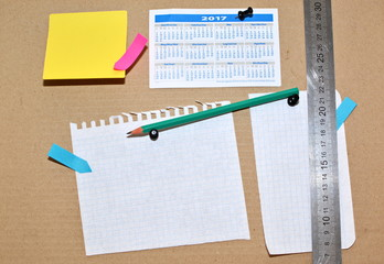 pinned cork message Bulletin Board with a clean sheet of paper for notes and announcements and calendar for the year, pencil, metal ruler