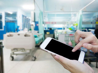 Woman using touch screen mobile phone with blurred image hospital