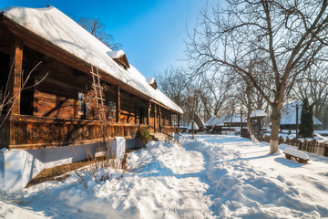 Fairy Tale Winter View with timber cottages at the Village Museum in Bucharest, Romania