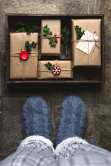 Feet with warm winter socks standing in front of Christmas gifts