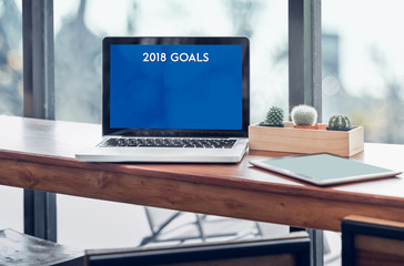 Goals for 2018 word in laptop computer screen with tablet on wood stood table in at window with blur background,Digital Business or marketing trending.