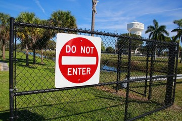 Red and White Do Not Enter Sign on Chain Link Fence with Deerfield Beach, Florida Identifying Water Tower in the Background Frame Right, Quiet Waters Park, Morning
