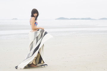 A woman in a bikini swaying on a beach playing with a blanket