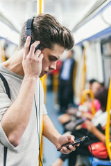 Young Man Listening Music in Subway