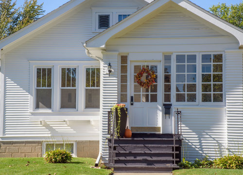 Exterior street view of cute bungalow home decorated for fall with Autumn wreath and pumpkin (address removed)