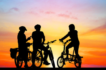 Groups of friends silhouette and bike on sunrise