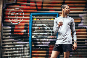 Young runner listening music with smartphone on the city.