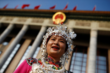 A delegate in traditional clothes poses for pictures as she arrives at the Great Hall of the People before the start of the closing session of the 19th National Congress of the Communist Party of China, in Beijing