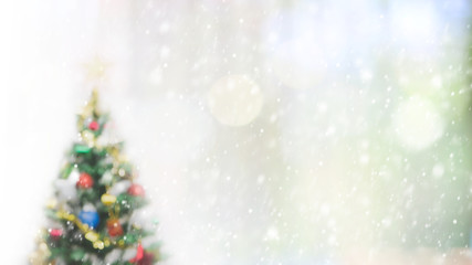 Blurred bokeh christmas tree with snowfall background for your text or advertising.